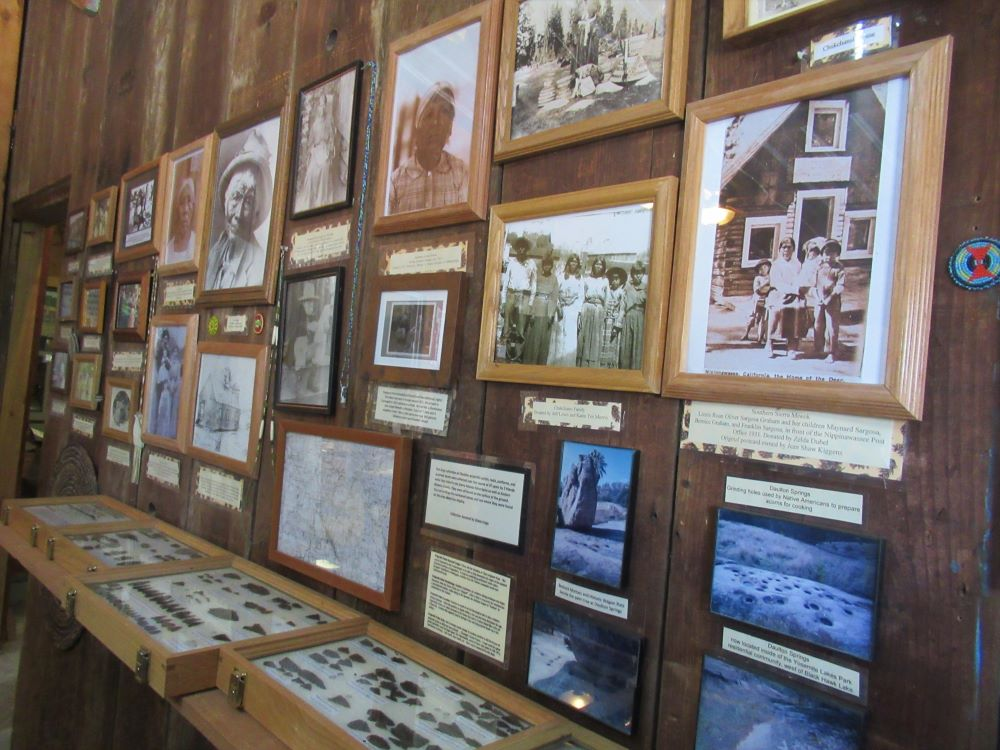 Displayed on a wall is a collage of old photographs of the Chukchansit people and their homes near Coarsegold