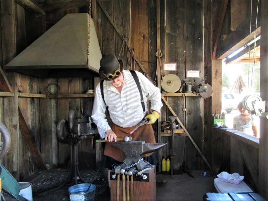 Photo of a blacksmith working on a large anvil.