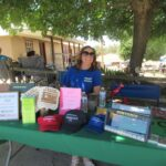 Photo of a volunteer who is selling merchandise at the Music in the Meadow event.